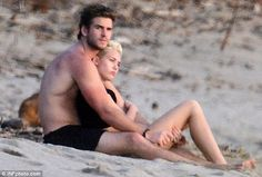 Snuggling in the sands: Liam Hemsworth wrapped fiancée Miley Cyrus in his arms as the pair sat on the beach and watched the sun set during a romantic holiday in Costa Rica