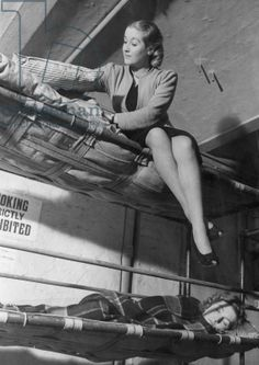A woman fixing her mattress and pillows on the top bunk as she prepares for a nights sleep in an air raid shelter during the Blitz, November 1940 (b/w photo)
