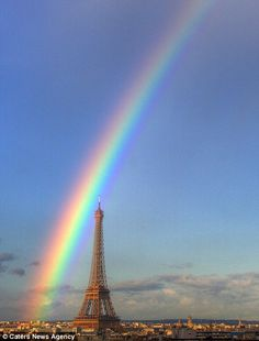This is the amazing image of a pair of rainbows surrounding the Eiffel Tower in Paris taken by a photographer from his living room window in his apartment which overlooks the historic landmark.