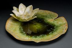"Platter is slab built and altered to create a lily pad form. Each lily flower leaf is made separately and assembled to produce a bowl reminiscent of a lily flower. White crystalline glazed flower reflects in the glass glaze of the pad. Crystals grown in a precise, 14 hour firing cycle to create crystals which look like a lily pad themselves. Lily pad is 14"". Pieces are both decorative and functional. Please close window to open another window."