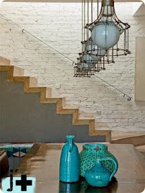 Méchant Design: Wood and concrete stairs, white bricks, stunning pendant lighting, and old turquoise pots.