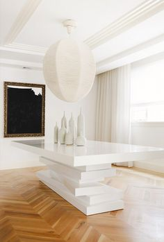 Jen Shalom monochromatic Brooklyn loft. Caption: Stacked Dining Table from Cuff Home, herring bone wood flooring.