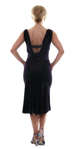 Purple velvet tango dress with draped back by conDiva. This design is made from stretch velvet and cut in a body hugging silhouette. The back is beautifully draped, and decorated with a lame strap across the open back that covers your lingerie. The skirt has two back triangle godets that add
