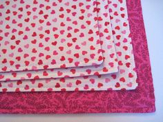 This set of cute reversible rectangle valentine placemats are made with a soft cotton fabric. Sold in sets of 4 (dark pink back) or 6 (lighter pink back). Made with 2 coordinating fabrics, one with an allover pattern of tiny bright pink, lighter pink and red hearts scattered on a white background. The reverse side is a coordinating pink vine print. Reversible placemats are double stitched on the edges to keep them looking great wash after wash. Lined with a thin layer of polyester batting to…