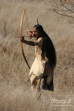 A young Native American Indian boy using or hunting with a bow and arrow aiming it at his target