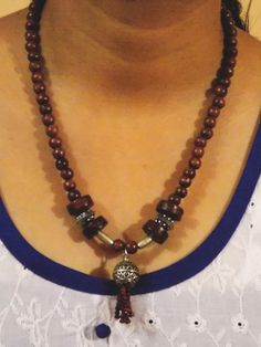 Wooden necklace with carved steel pendant and other steel beads. This is an awesome design for those who love to wear fashionable jewelry.