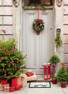 A festively decorated front porch, complete with a miniature Christmas tree and presents.