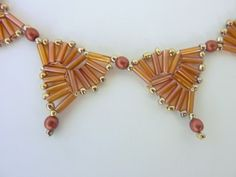 DIY Jewelry: FREE beading pattern for necklace woven with bugle beads and 10/0 seed beads into a string of triangles making a lovely geometric design.