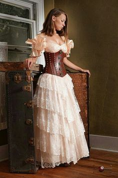 597c28e67475 From the Steampunk Fashion Guide to Skirts   Dresses  Tiered Skirts - An  example of a woman dressed in a victorian style long lace tiered ruffle  skirt.