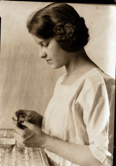 A woman is photographed while inserting filaments into small light bulbs, ca 1925.