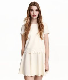 Natural white. Short-sleeved top in crêped jersey with a cut-out pattern at hem and scalloped trim at cuffs and hem.