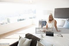 Stock Photo : Senior woman sitting on bed and looking at tablet computer