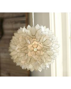 "Hundreds of capiz-shell petals form a luminous lotus flower. The petals are trimmed with polished nickel. Overall: 15"" diameter, 15"" high Hangs from a clear cord with an 18"" decorative chain On/off switch on plug-in cord. Hinged door at bottom of pendant allows for bulb changes."