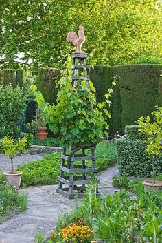 LES CONFINES, PROVENCE, FRANCE - DESIGNER: DOMINIQUE LAFOURCADE - POTAGER/ KITCHEN GARDEN WITH WOODEN TRELLIS TOPPED WITH A COCKERILL