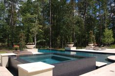 This spa and swimming pool with its high contrast black tile and travertine coping are engaged with additional drama including an infinity edge spa and pool.