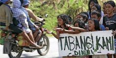"""Kids after Typhoon Bopha hits Philippines. """"TABANGI KAMI"""" means help us. They are asking for food to people and vehicles passingby."""