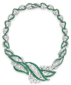 AN EMERALD AND DIAMOND NECKLACE, BY OSCAR HEYMAN & BROTHERS   Designed as a variously-shaped diamond graduated band of foliate motif, trimmed with calibré-cut emeralds, mounted in platinum, 1956, 15¾ ins.  With maker's mark for Oscar Heyman & Brothers