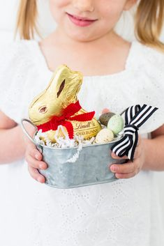 These mini DIY Easter Baskets make the perfect gift for friends, neighbors and teachers! Start with a small basket or mini galvanized bucket. Add paper grass as the base and tie a cute ribbon bow on the handle. Place a Lindt GOLD BUNNY in the basket, then fill with small Easter eggs and other Lindt Easter chocolates. It's simple to create these perfect mini Easter basket gifts! Find more Easter Lindtspiration on the Lindt Chocolate Blog! #Sponsored #MyLindtEasterBasket #LindtPartner