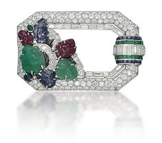 An Art Deco Multi-Gem and Diamond Brooch, by Mauboussin - The pavé-set diamond openwork hexagonal frame decorated with carved emerald, sapphire and ruby leaves, enhanced by black enamel detail, to the calibré-cut emerald, sapphire and baguette-cut diamond bombé motif, 1920s