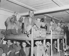 Ebensee Survivors Wave to Liberators  (May 8, 1945)  Survivors wave to American liberators from their bunks in the infirmary barracks for Jewish prisoners in the Ebensee concentration camp.