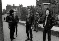 """The Clash photographed in October 1977 in Belfast by Adrian Boot, after their gig at Belfasts Ulster Hall got cancelled, officially because of insurance problems but with rumours suggesting that Joe Strummer had received a death threat. The cancellation resulted in heavy handed police enforcement which left the disappointed fans and the band angry, sad, confused and helpless. """"…So instead of a sound check I was to do a photo-session with the Clash, a simple walk about, black and white…"""