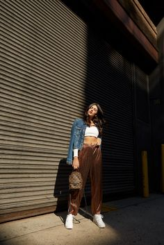 New York Fashion Week Street Style September 2017 - Julia Friedman wears a Nasty Gal cropped sweater, Paige Denim Jacket, House of Harlow Kate Pants from Revolve Clothing, Nike Air Max Sneakers, and a Louis Vuitton Backpack.