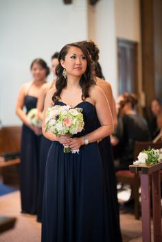 Elegant navy bridesmaid dresses, traditional wedding.  Green, light pink, peach and white bouquets.