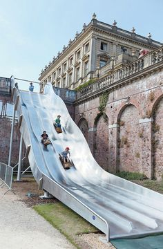 People use the giant slide at Cliveden House, Berkshire. (REX/Solent News)