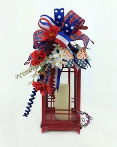 This Lantern Swag fits an 13-18 lantern and contains red flowers, a patriotic heart ornament, and red white and blue curly sprays. This