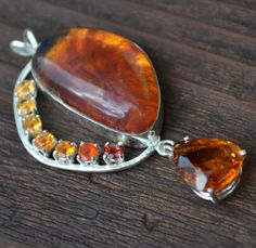 A large amber cabochon is accented with a pear shaped citrine and smaller citrines, a fire opal and a garnet in this graceful necklace. The roughly