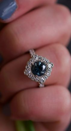 With ethical sourcing as a priority, we sourced this stunning ethical Montana sapphire as the center stone, and surrounded it with a floral halo of ethical moissanites. A halo of milgrain detailing surrounds each layer of stone, nodding to classic vintage design elements. This custom engagement ring was designed by Abby Sparks Jewelry in Denver, Colorado. #ethicalengagementring #montanasapphire #moissaniteengagementring #customdesign #denverjewelry #whitegoldjewelry #wedding…