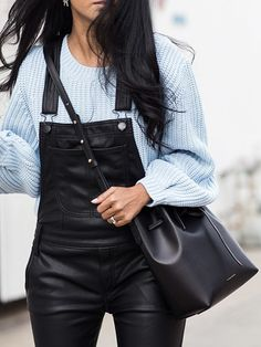 Leather overalls paired with a long knit sweater.