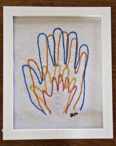 Trace each member of the family's hands, then stitch in different colors.