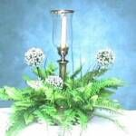Elegance includes a hurricane lantern with tapered candle surrounded by fern and flowers.