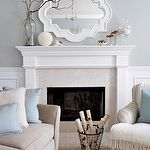 source: Centsational Girl  Chic living room design with gray walls paint color, Casbah mirror painted white, fireplace, tan sofa, blue pillows and wainscoting.