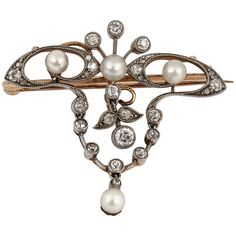 19th Century Natural Pearl Diamond Silver Gold Floral Brooch. Late 19th Century natural pearl and diamond floral brooch/pendant mounted in gold and faced in silver.