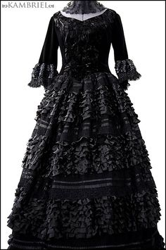 This darkly enchanting couture Black Countess gown by Kambriel is made from an exquisite combination of decadent black fabrics. The fitted, princess seamed bodice has a sweetheart neckline and is made from an incredibly supple, soft to the touch jet black velvet, subtly accented with crushed black velvet at the center front, and lined with softly luminous silver crushed taffeta that gleams like moonlight. The 3/4 length, soft velvet sleeves culminate in ruffled flounces embellished with...