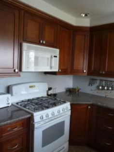 White Kitchen Appliances With Wood Cabinets dark floor, dark cabinets, white appliances, light countertop