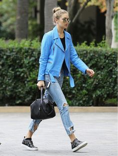Gigi Hadid wears a black top, blue moto jacket, distressed jeans, slip on sneakers, aviator sunglasses, and a black duffle bag