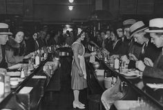 A waitress stands in the middle of the counters during lunch time at the Exchange Buffet in New York City in the 1920s