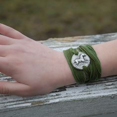 The range of textures, from the hammered, light reflecting pewter to the richly colored silk create a contemporary look to wrap around your wrist. The silk strip is wrapped sveral times around the wrist and then tied. Available with emerald green or midnight blue silk.