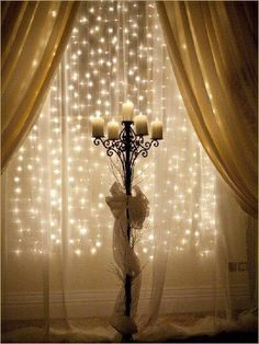 Strings of mini lights attached to a tension rod behind sheer fabric