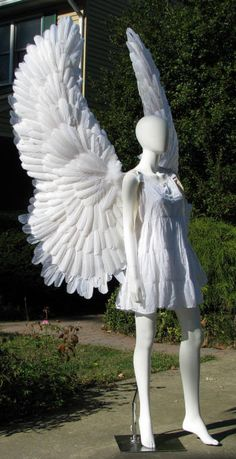 Huge White Upraised Angel Costume Wings have wire through the backstrap into each wing, allowing them to be positionable as seen in this picture