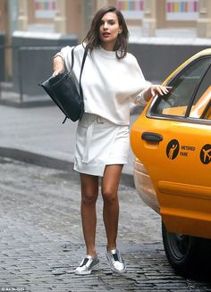 Casual chic: For the shots, the model donned a white wraparound skirt, belted at the waist, paired with a long-sleeved baggy sweater