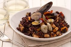 Il riso nero ai frutti di mare è un primo piatto molto particolare, formato da un aromatico riso venere dall'elegante e naturale colore nero,  arricchito con cozze, vongole, gamberi e pomodorini.