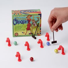 Miniature marbles version of Croquet, a traditional summer game, but with this product you can play it all year round on your dining room table!   Use whatever's handy to build a course with obstacles and things to shoot through, Then grab a mallet and get whackin'! Great pocket  sized marble game to take on the go!