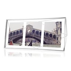 "Umbra Prisma Multi Picture Frame, Chrome - Display your photos in the elegant and contemporary Prisma multi photo display frame by Umbra. Each frame is made of metal wire and floats three 5x7"" photos or two 5x7"" photos vertically between two pieces of glass. Prisma can sit vertically or horizontally and can be mounted to the wall or used ..."