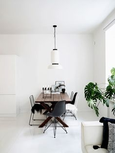 scandinavian-designed dining room with black accent chairs and statement lighting