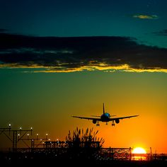 Beautiful Sunset...as an AIRPLANE lands on a runway.