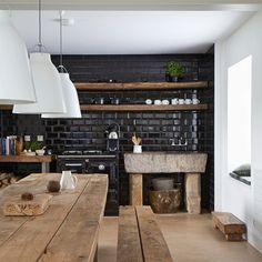 See all our kitchen design ideas, including this country kitchen with glossy black tiles and reclaimed materials